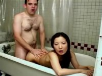 Asian slut fucking a white hunk in a tub
