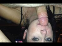 A  dark haired honnie is on her back getting her face stuffed with cock
